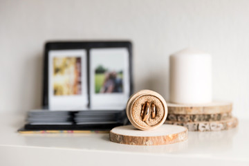 Wedding rings on the wooden stand, hygge scandinavian home with candle and family photoalbum