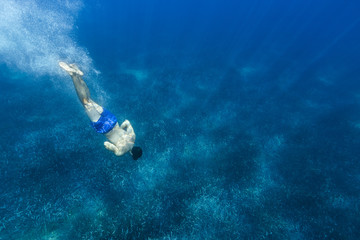 Young man in a blue shorts diving to the bottom of the Medittera