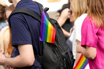 Concept of sexual minority. Young man with rainbow flag on his backpack