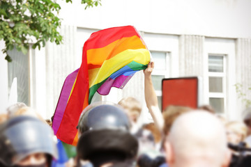 Concept of sexual minority. Man holding rainbow flag during gay parade outdoors