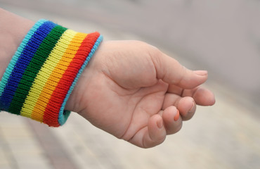 Concept of sexual minority. Female hand with gay rainbow wristband outdoors