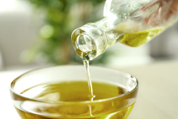 Pouring hemp oil from bottle into glass bowl on blurred background, closeup