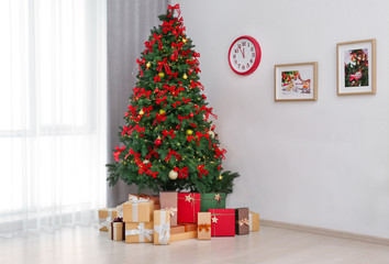Beautiful Christmas tree with gifts in room