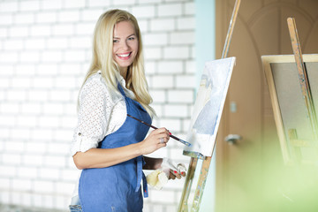 smiling woman artist with a brush in her hand draws on canvas