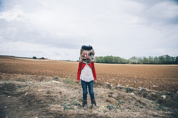 Child in scarecrow mask on field