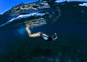 Snorkeling woman dives to sea bottom. Snorkeling girl in full-face snorkeling mask.
