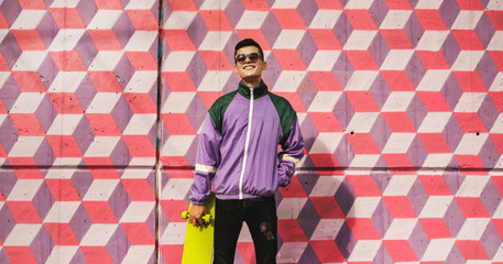 Wild kids/portrait hip young male in trendy outfit in front of colorful patterned wall.
