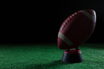 Close-up of American football standing on holder on artificial