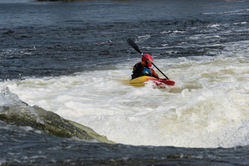 Kayaker running short rapids