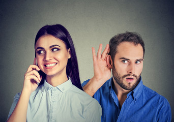 A cheating girlfriend. Curious man secretly listening to a happy woman talking on mobile phone with her lover