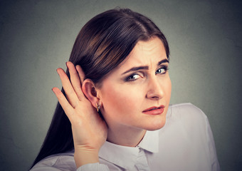 Woman with a hearing loss cupping her hand behind ear to try and amplify available sound