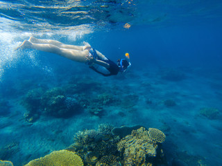 Snorkeling girl in full-face snorkeling mask. Coral reef in shallow sea.