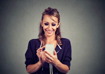 Happy young woman looking at her smart phone