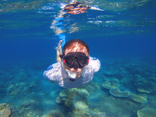 Young man underwater portrait. Male snorkel in tropical lagoon undersea photo