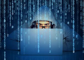 Man hacker working on a laptop on binary code background