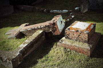 Umgefallenes Grabkreuz auf einem alten Friedhof