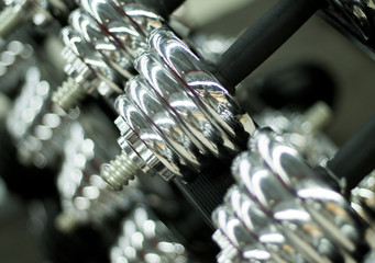 Shiny dumbbells in gym closeup photo. Metallic dumbbells or barbell weights.