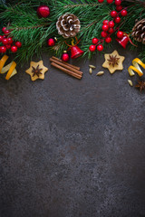 Christmas background border of fir branches and Christmas toys and spices. Top view with copy space