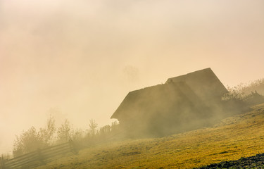gorgeous autumnal countryside scenery abandoned barn on hillside in sick fog at sunrise