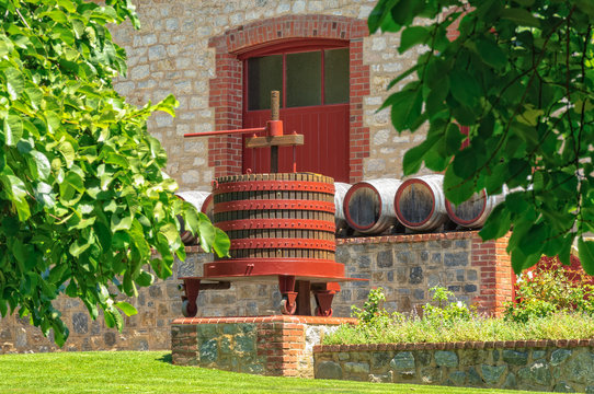 Grape press and barrels in front of a cellar door of Yalumba Winery in the Barossa Valley - Angaston, SA, Australia