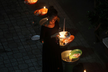 Woman walks with an offering of food and money while praying for loved ones who have passed away, during Pchum Ben festival, or the festival of the dead, in Phnom Penh