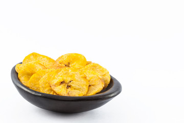 Plantain fried coins in a traditional black clay bowl isolated on white background