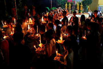 People carry offerings of food and money while praying for loved ones who have passed away, during Pchum Ben festival, or the festival of the dead, in Phnom Penh, Cambodia