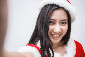 Pretty asian woman wearing santa custume for Christmas time take a self portrait with her smart phone outside, Asian girl selfie,