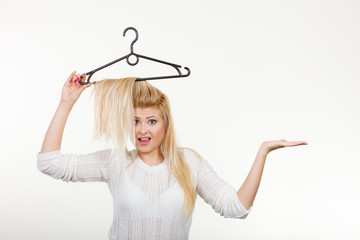 Blonde woman holding hair on clothes hanger