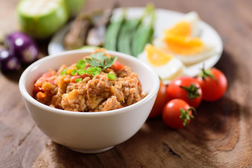 Thai Northern food (Nam Prik Ong) with vegetables on wooden background,spicy tomato with pork,red chili dip,NorthernThai dipping sauce