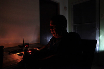 Juan Rivera sits at his home during a blackout after Hurricane Irma rolled by the U.S. territory's northern coast, in San Juan