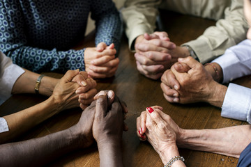 Group of interlocked fingers praying together Wall mural