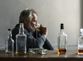 Elderly man sitting drinking whiskey alcoholic addiction bad habit