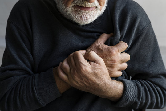 Closeup of elderly man having heart attack chest pain