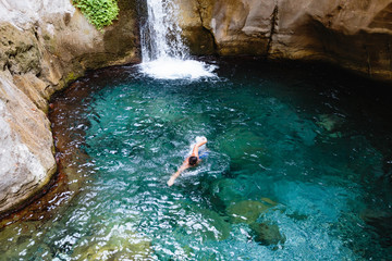 Man swimming in crystal clear water near small waterfall