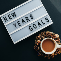"""GOALS"" text on desk and cup of cocoa on black background, top view, flat lay"