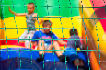 blurry abstract background, the boys play on the trampoline, can be used for illustration of articles about childrens entertainment