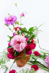 Floral design. A beautiful bouquet of pink peonies, cornflowers and red roses