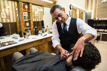 Professional barber in process of shaving young man in chair using razor
