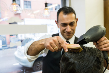 Smiling adult man working in barbershop setting hair of customer using hairdryer.
