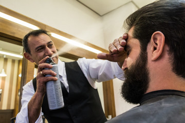 Professional barber applying hair spray to style hair of male customer.