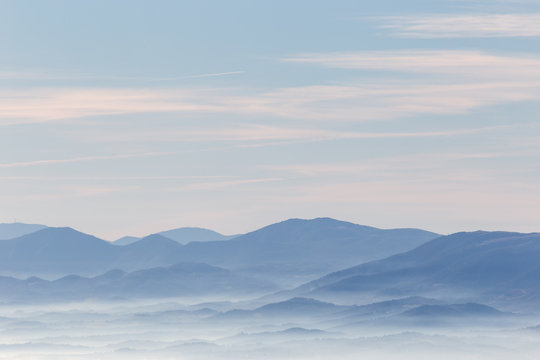 A view from above of a valley filled by a sea of fog, with various layers of emerging hills and mountains with different shades of blue
