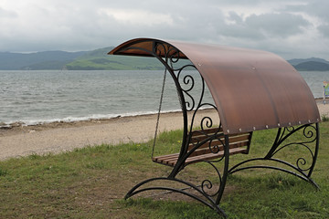 Forged swing with a roof by the sea.
