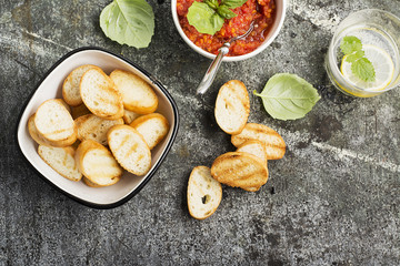 Healthy snack or lunch. Homemade tomato vegetable sauce with garlic, herbs, salt, butter, spices, fresh basil in a ceramic bowl with grilled toasts on a gray stone background. Top View.