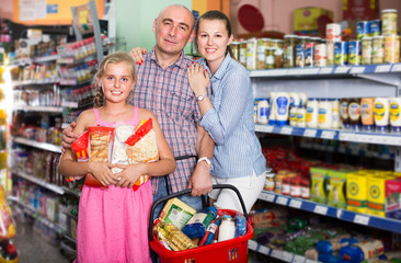 Parents with child are standing with basket of purchases