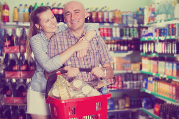 Happy woman and man with shopping basket