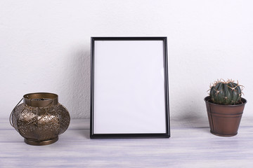 Photo frames next to decorative objects and lavender flower on white and blue wood table. Decor.