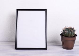 Photo frame next to cactus on wooden table. Decor.