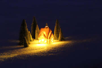 Christmas card.  house in a snowy fir forest. light out the window in the dark. Christmas concept.