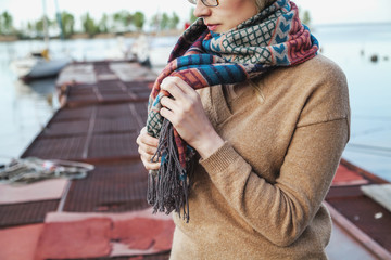 Young woman tying scarf on mooring